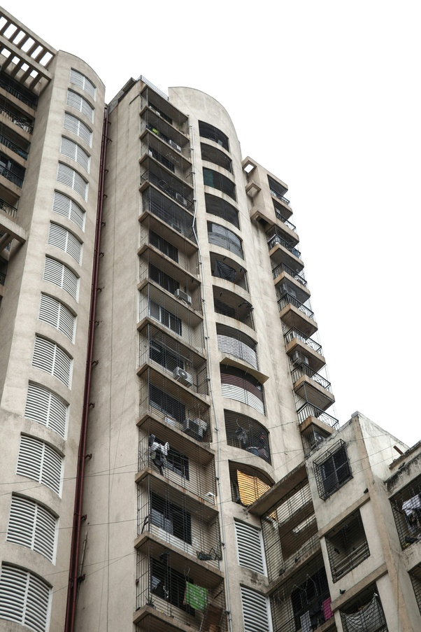 What is preferable buying a house or investing in mutual funds depicted by a multistory housing complex